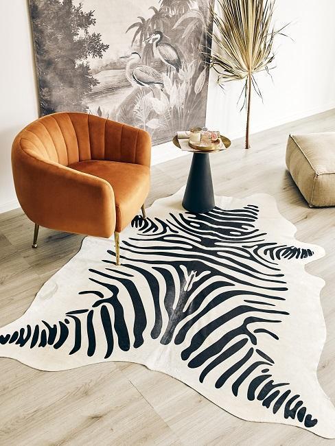 Fragment salonu z pomarańczowym fotelem, dywanem z zebrę oraz skórzanym pufem