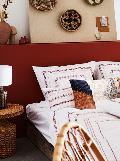 Sypialiania w stylu etno z plecionym stoliiem nocny, poduszkami oraz moodboardem z pamiętek