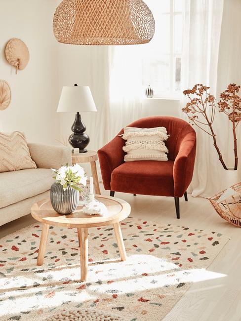 jasny salon z beżową kanapą, pomarańczowym sotelem, stolikiem oraz dekoracjami