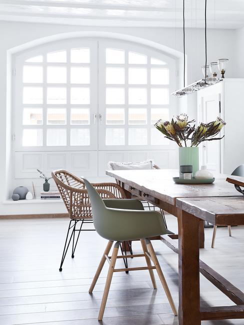 biała jadalnia w stylu skandynawskim z różnymi krzesłami, dużym, drewnianym stole oraz wazonem z kwiatami
