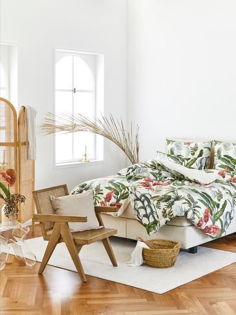 Biała sypialnia z łóżkiem z pościelą w tropikalne wzoy, rattanowym krzesłem i parawanem oraz koszem