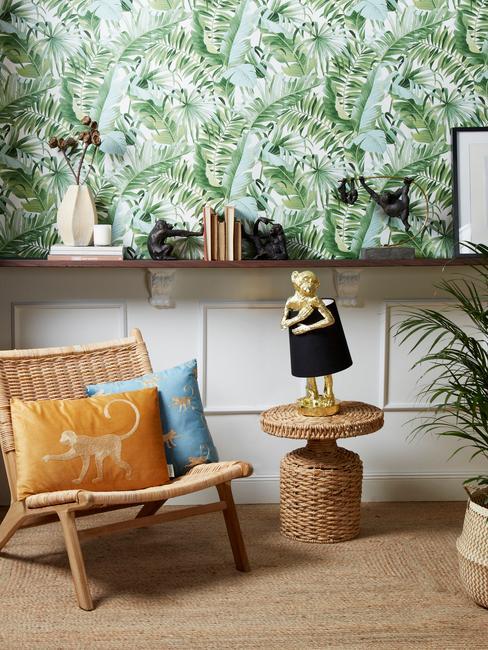 salon z tropikalną tapetą na jednej ścianie, rattanowym krzesłem i stoliczkiem oraz metalową lampą w kształcie mapłki