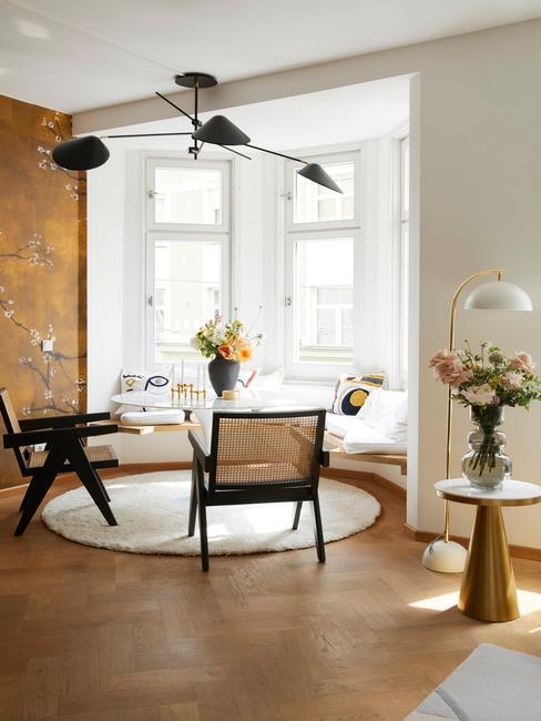 Kącik jadalny ustawiony salonie ze złotą ściną oraz dekoracjami