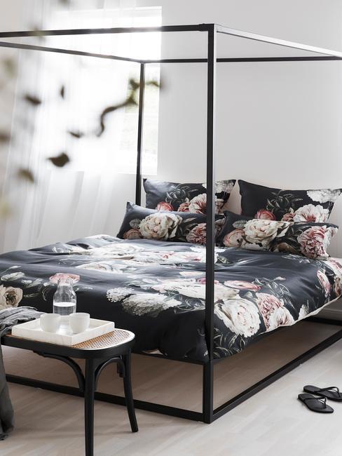 Zbliżenie na łóżko o czanej metalowej ramie z ciemną pościalą przed którą jest postawiony czarny, rattanowym stolik