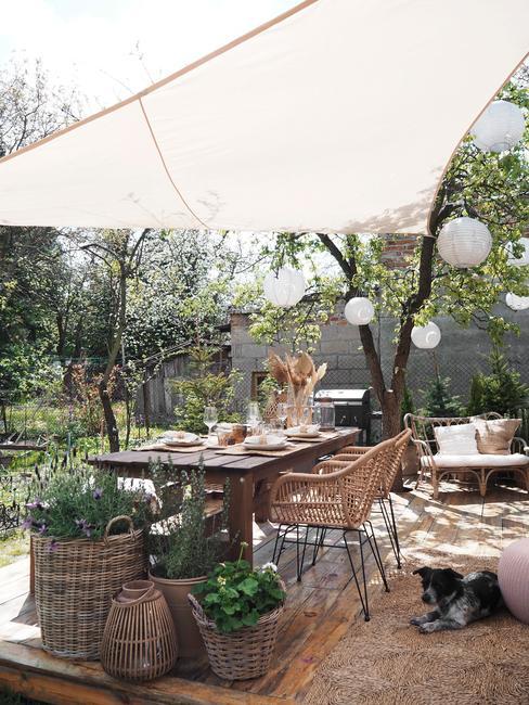 Fargment tarasu z rattanowym krzesłem, drewnianym stołem oraz roślinami w koszach