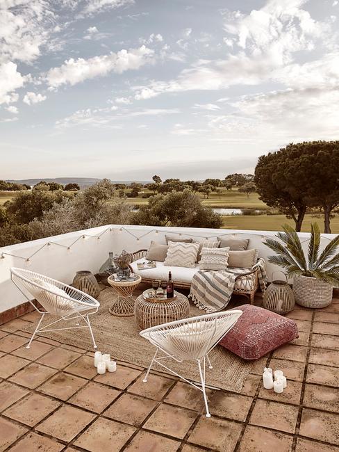 Taras z dwoma krzesłami, sofą, pufami oraz dużynmi roślinami