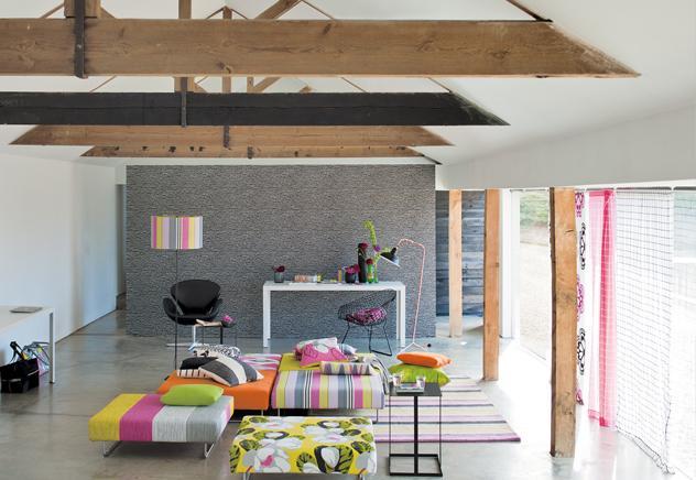 En un mismo espacio conviven el estar y la zona de trabajo. Con una decoración de líneas marcadas y piezas de corte contemporáneo, el ambiente se llena de vida gracias al uso de colores brillantes y a una mezcla genial de estampados.