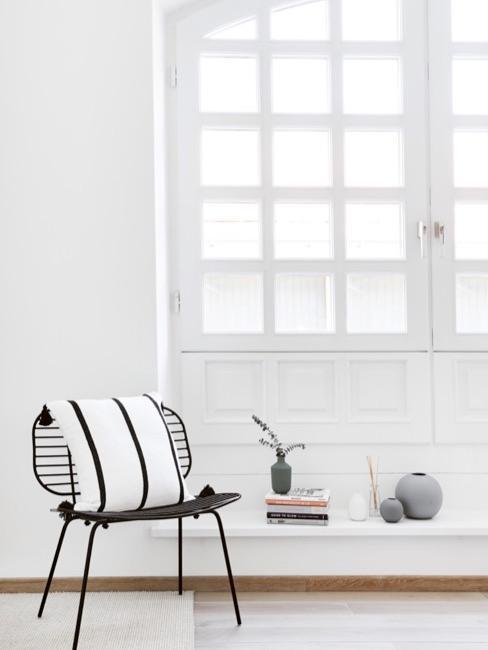 Stuhl und Deko vor großem Fenster