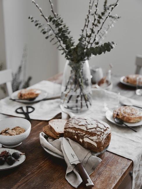 Gedeckter Tisch mit schwarfem Brotmesser in der Mitte