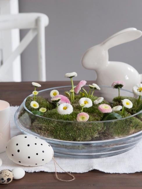 Tisch mit Osterdekoration wie Osterhasen, Blumen und Ostereiern