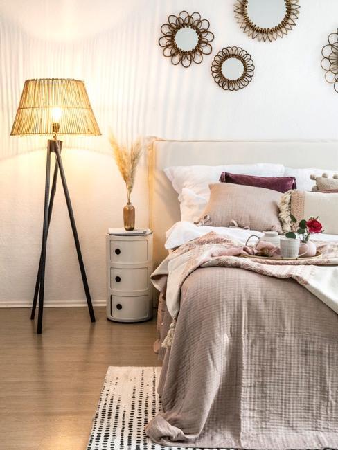 Sypialnia boho z dekoracjami ściannymi oraz lampą