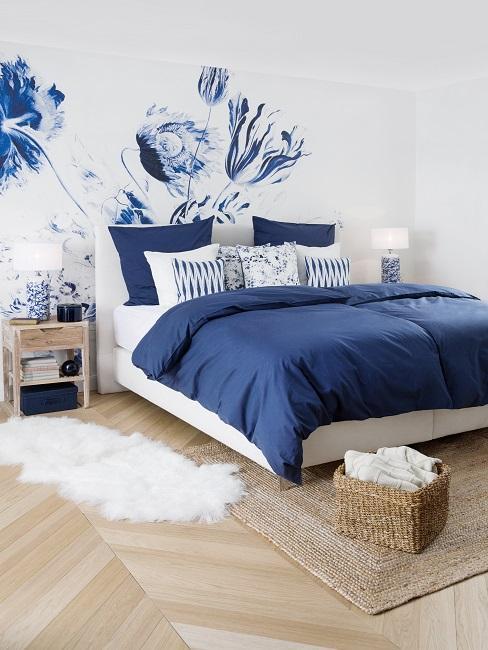 Łóżko z ciemnoniebieską pościelą przed ścianą z kwiatową tapetą w kolorze niebieskim i białym