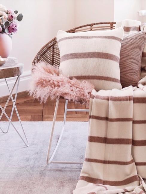 Rosa Fake Fur Sitzauflage auf Rattan Sessel dekoriert mit Kissen neben Beistelltisch
