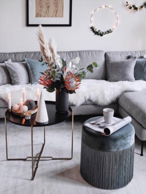 Salbeigrüne Wohnzimmerdeko kombiniert mit weißem Schaffell auf grauem Sofa