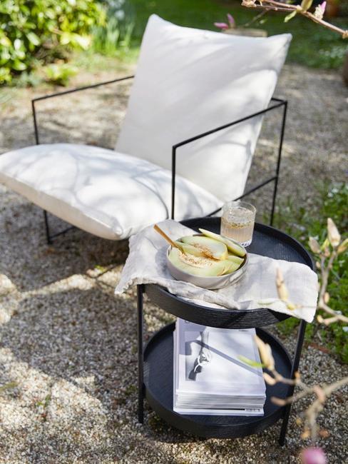 Metallstuhl mit heller Polsterung und schwarzer Beistelltisch auf Terrasse