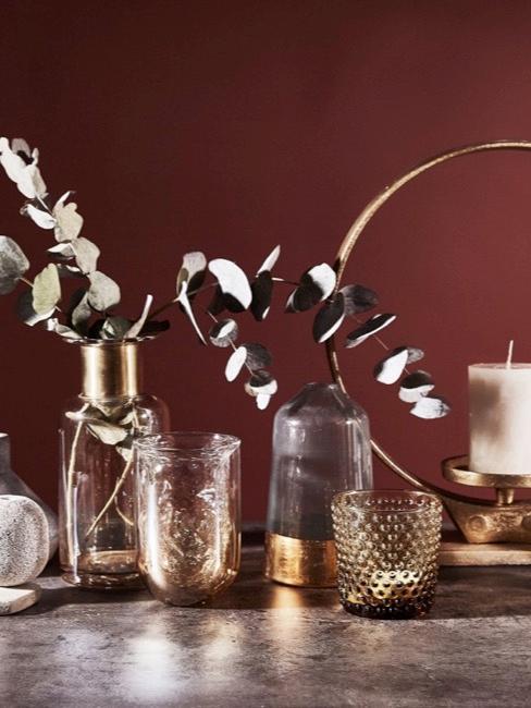 Kleine Vasen mit Deko auf einem Tisch neben einer Kerze