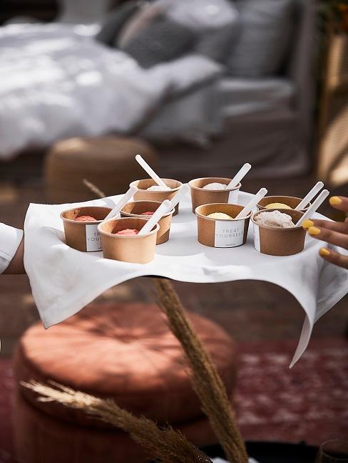 Eis in kleinen Bechern aus Pappe auf einem Tablett mit weißem Leintuch