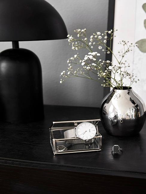 Dekogegenstände und eine schwarze Tischleuchte auf einer Kommode