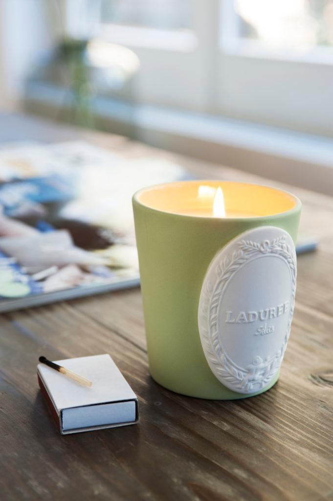 Duftkerze auf einem Holztisch, daneben eine Streichhölzerpackung
