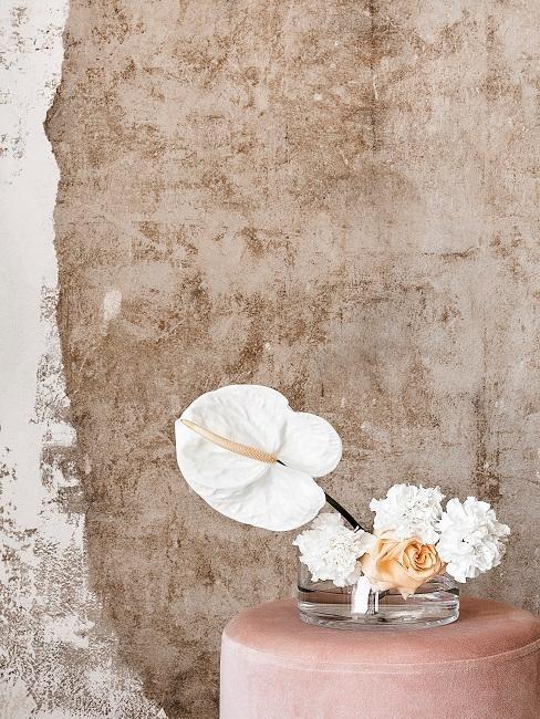 Weiße Calla in durchsichtiger Vase auf rosa Samtpouf