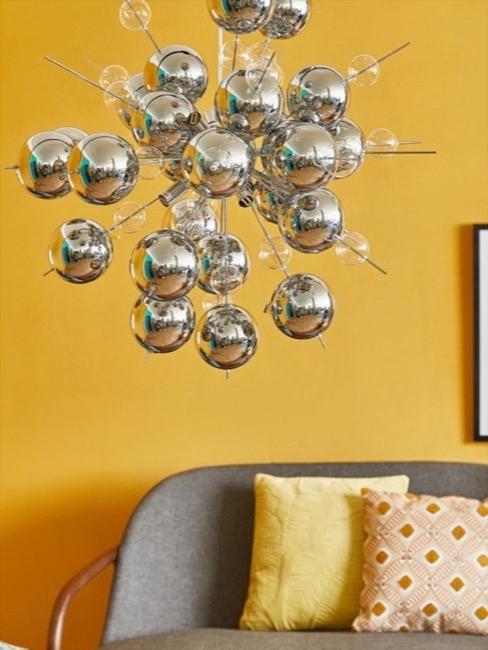 Parete gialla senape e divano grigio con lampadario argento