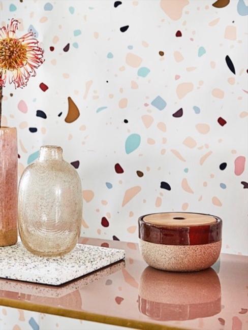 Consolle di fronte alla carta da parati in terrazzo bianco, rosa e azzurro con decorazione di vasi in vetro e lattine decorative
