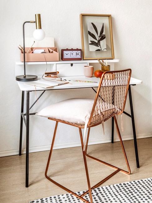 Małe biurko w kawalerce. Na nim artykuły papiernicze, złota lampka i obraz.