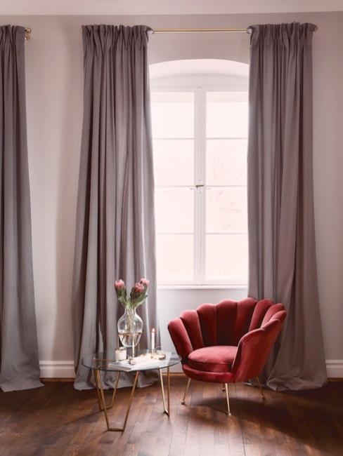 Fauteuil enveloppant rouge face à une table avec un pot de fleurs et devant une grande fenêtre avec des rideaux