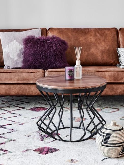 Brązowa skórzana sofa ze stolikiem kawowym i elementami dekoracyjnymi.