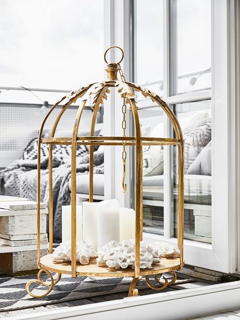 Ozdobna złota klatka dla ptaków ze świecami jako dekoracja balkonu.