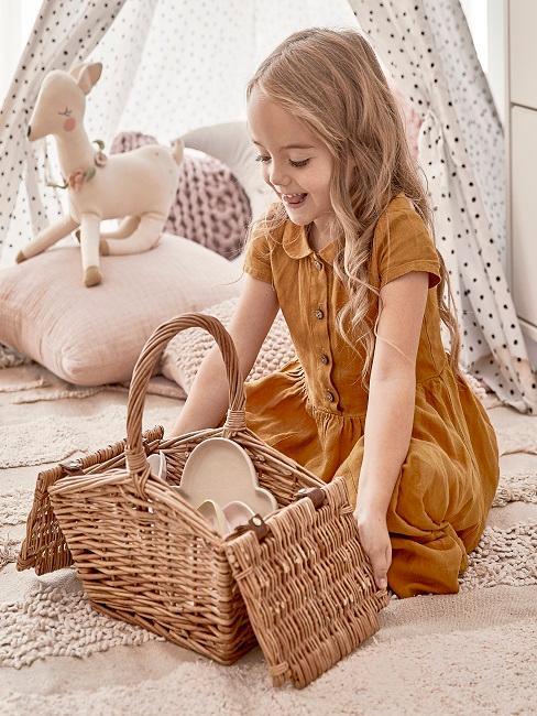 Kleines Mädchen öffnet freudig einen Picknickkorb.