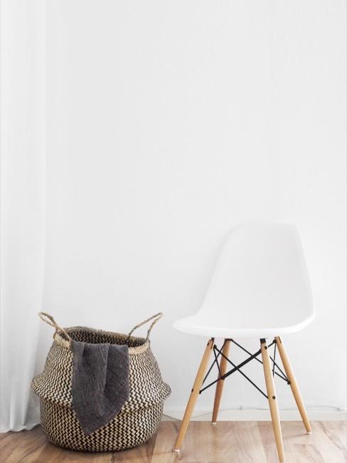 Kosz na pranie obok białego krzesła