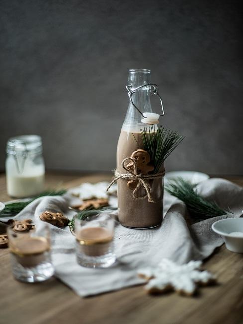 Szklana butelka z kokarką na stole z zimowymi dekoracjami