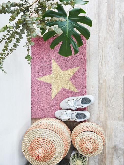 Różowa mata wejściowa z motywem gwiazdami, elementy dekoracyjne, rośliny oraz białe buty