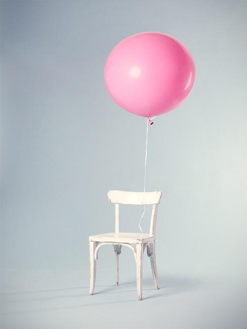 Weißer Stuhl mit rosafarbenem Ballon in leerem Raum