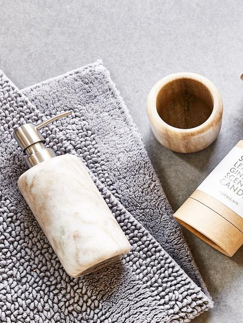 Edler Zahnputzbecher mit passendem Seifenspender auf einem grauen Handtuch