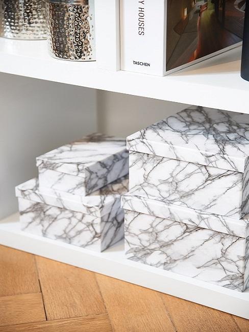 Aufbewahrungsboxen in marmorierter Optik in einem Regal