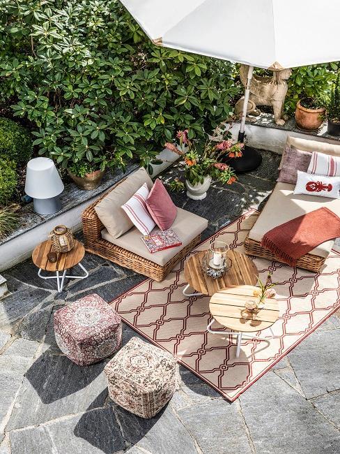 Sonnenschirm im Sonnenschirmständer auf einer Terrasse mit Terrassenmöbeln