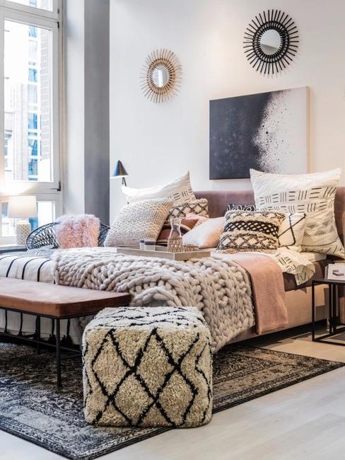 Stanza in stile boho con motivi geometrici e ampio letto, pouf