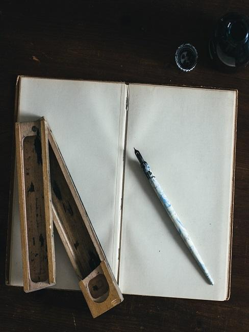Offenes Notizbuch auf einem Tisch, darauf ein Füller mit Tinte und ein Fülleretui aus Holz zum Kalligraphie Üben