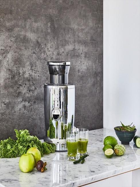Srebrna sokowirówka w kuchni i dwie szklanki z zielonym koktajlem