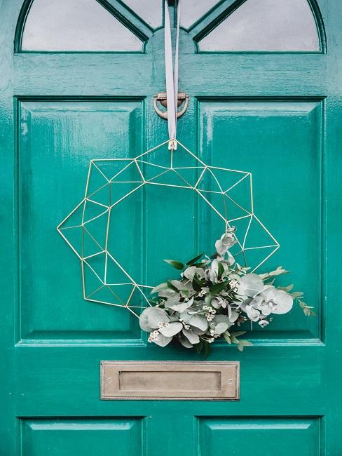 Turkusowe drzwi wejściowe do domu wraz z wiszącym na nim metalowym wieńcem w kształcie gwiazdy