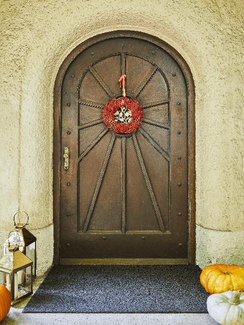 Braune Haustür mit rotem Kranz und Laternen und Kürbissen als Deko