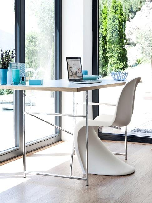 Ein Schreibtisch vor einer Fensterfront in der Ecke, dazu ein moderner Designerstuhl in Weiß