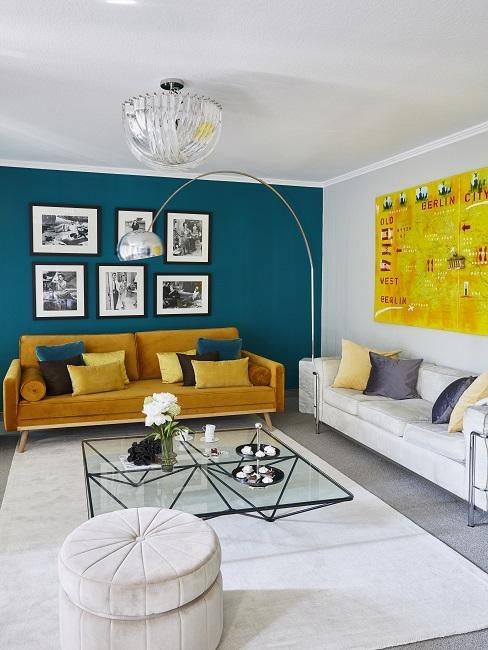 Wandfarbe Petrol im Wohnzimmer als Akzent an einer Wand mit gelbem Sofa und weißem Teppich