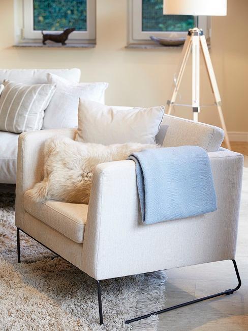 Der Sessel neben dem Ecksofa in Creme mit kuscheligem Kissen und Plaid im Wohnzimmer von Jana Ina Zarrella