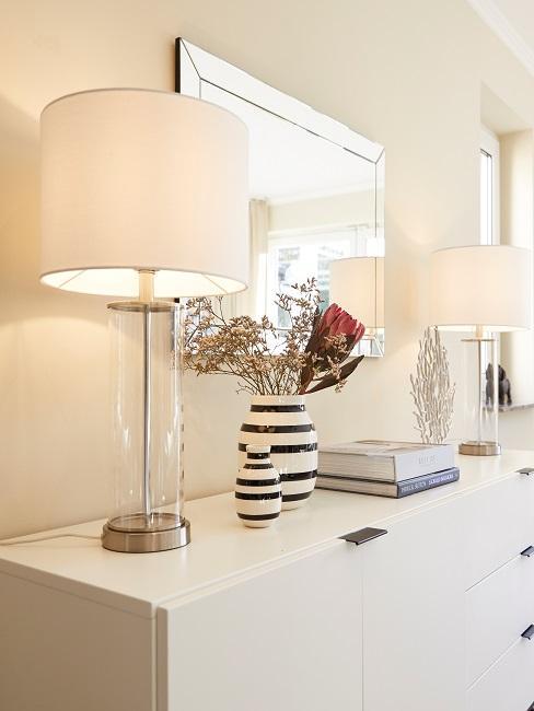 Das weiße Sideboard im Wohnzimmer von Jana Ina Zarrella mit Lampen und Deko und einem Spiegel darüber