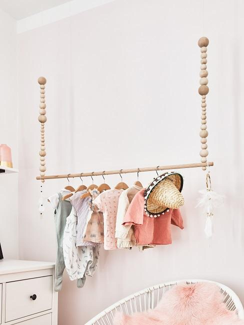 Hängende Garderobe aus Holz an einer Wand im Luxus Kinderzimmer mit dekorativ aufgehängter Kleidung