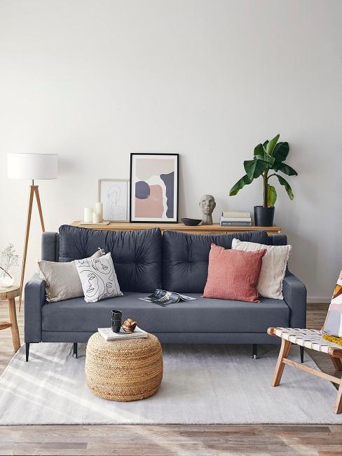 Graues Sofa mit Pouf aus Jute neben Kissendeko, Wandbildern und einer Pflanze
