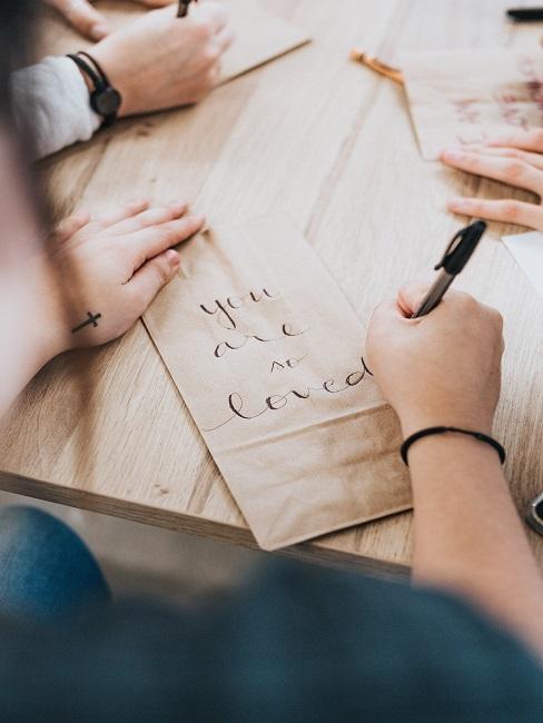 Person schreibt Schriftzug auf brauner Papiertüte